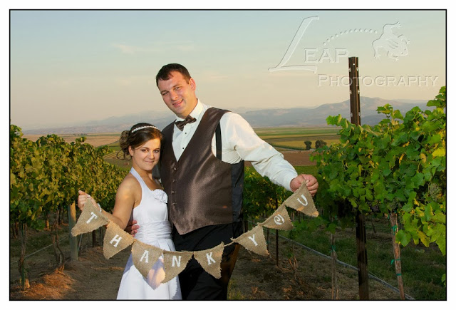 bride and groom standing in a vineyard holding a thank you sign