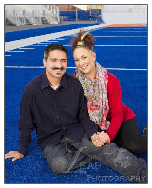 newly engaged couple on the BSU blue turf