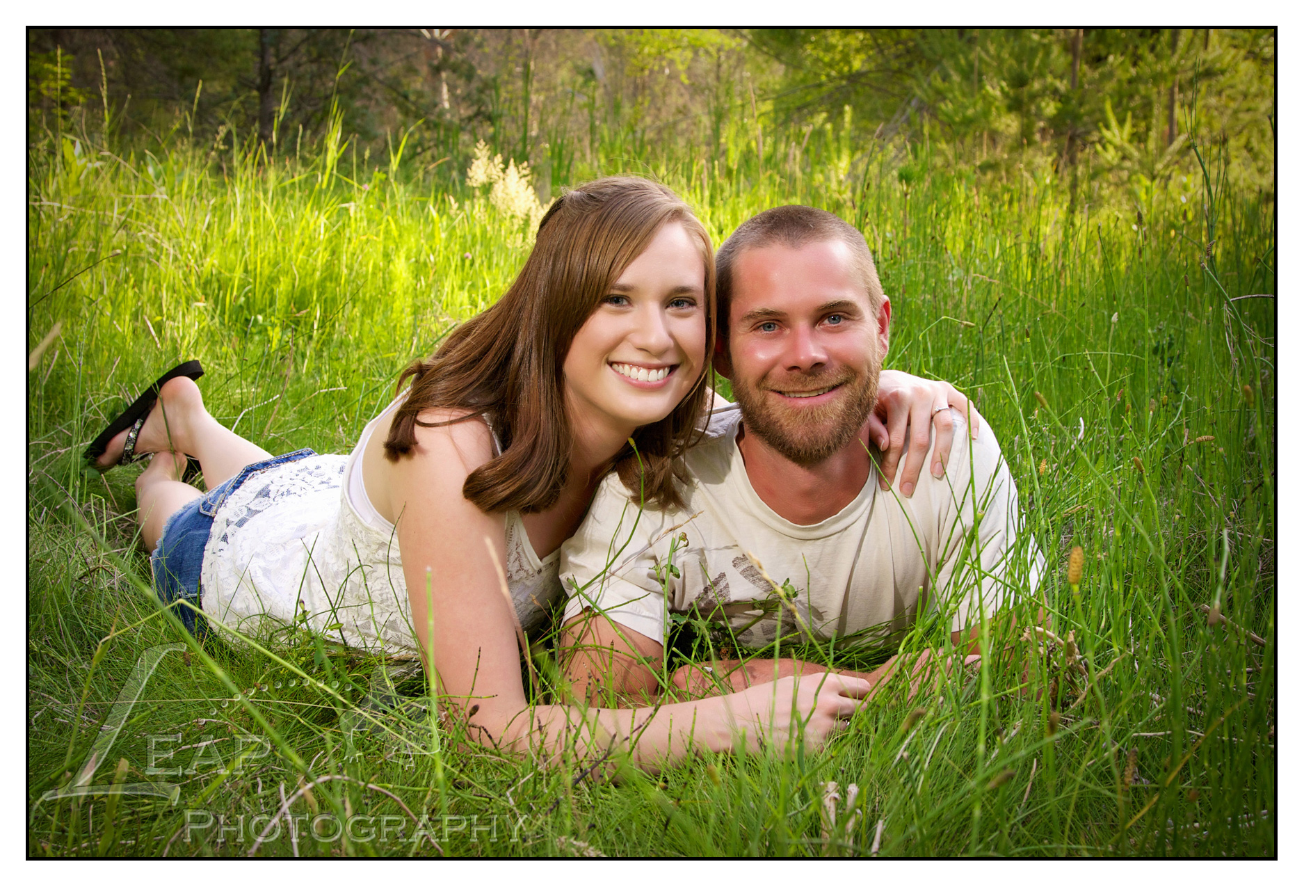 young couple laying in the grass