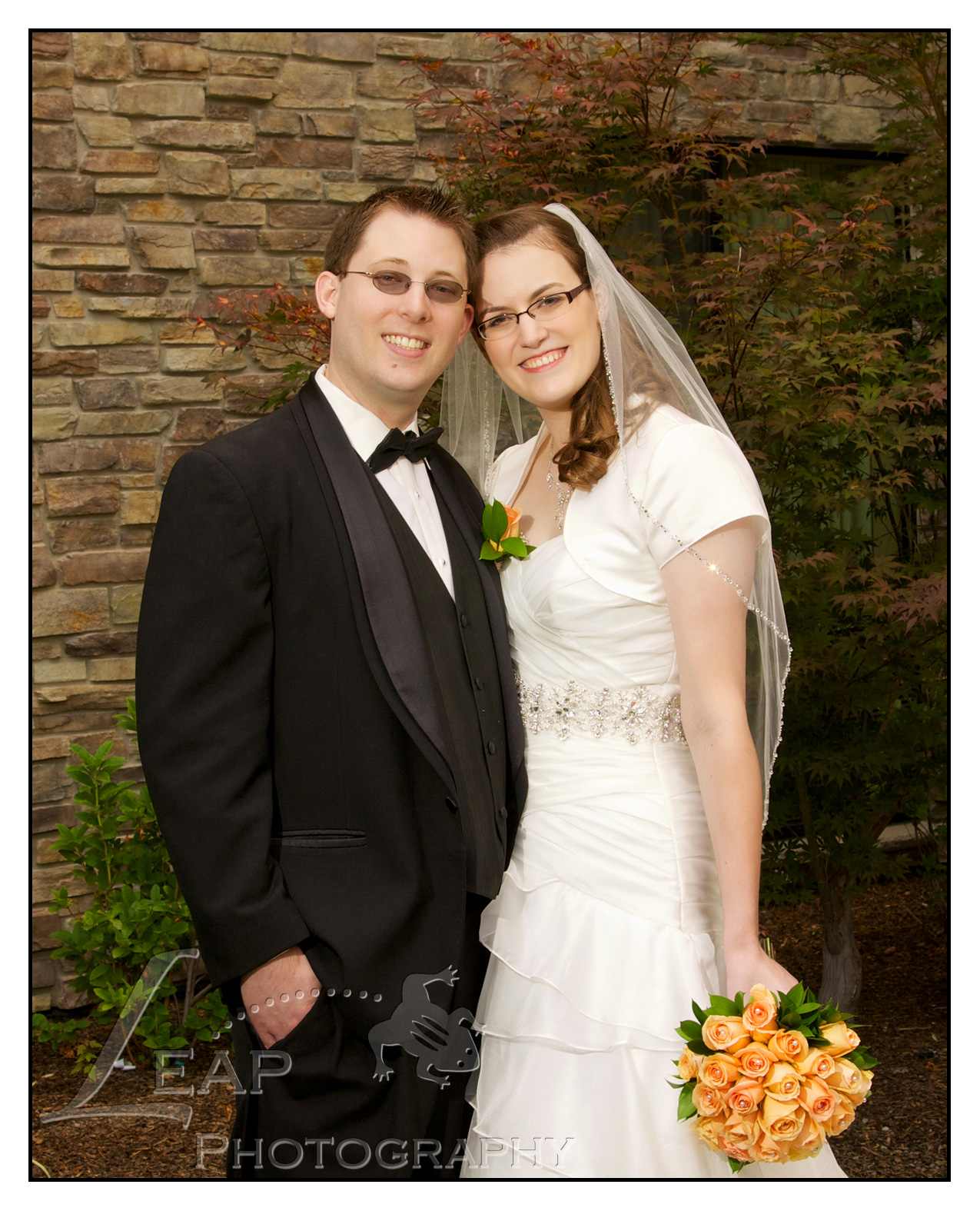 bride and groom in front of a brick wall