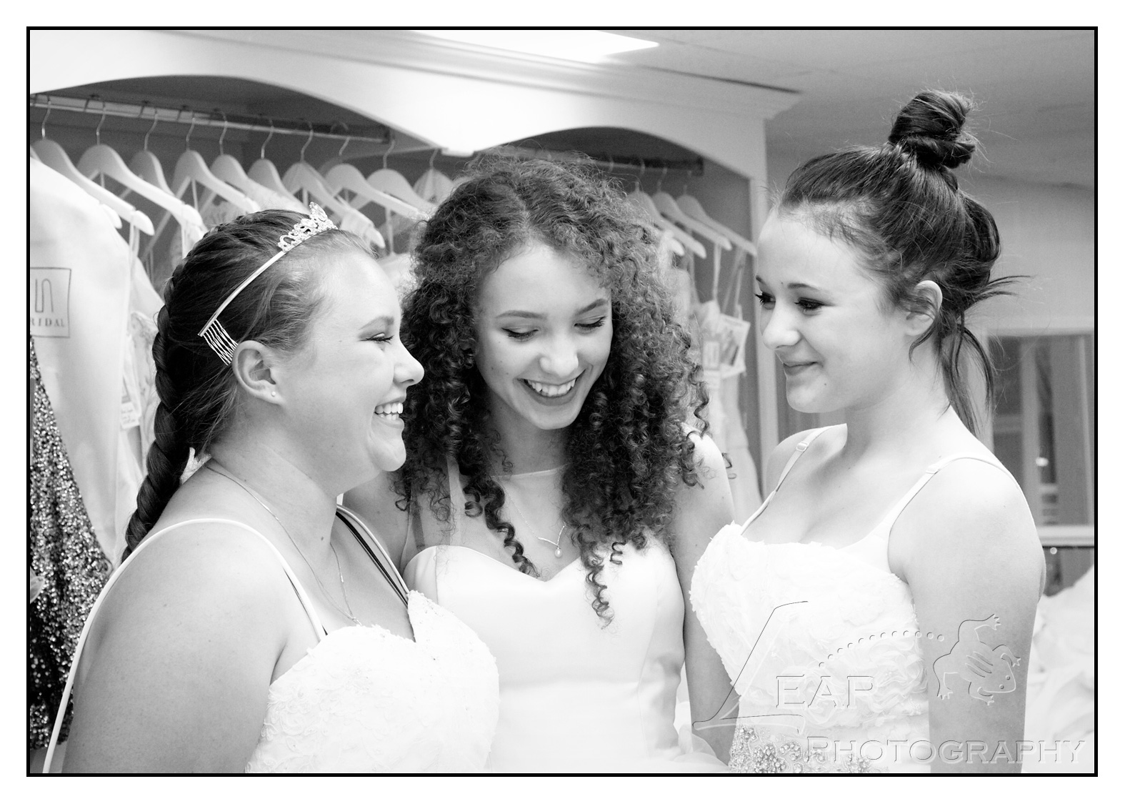 3 sisters laughing, in bridal gowns