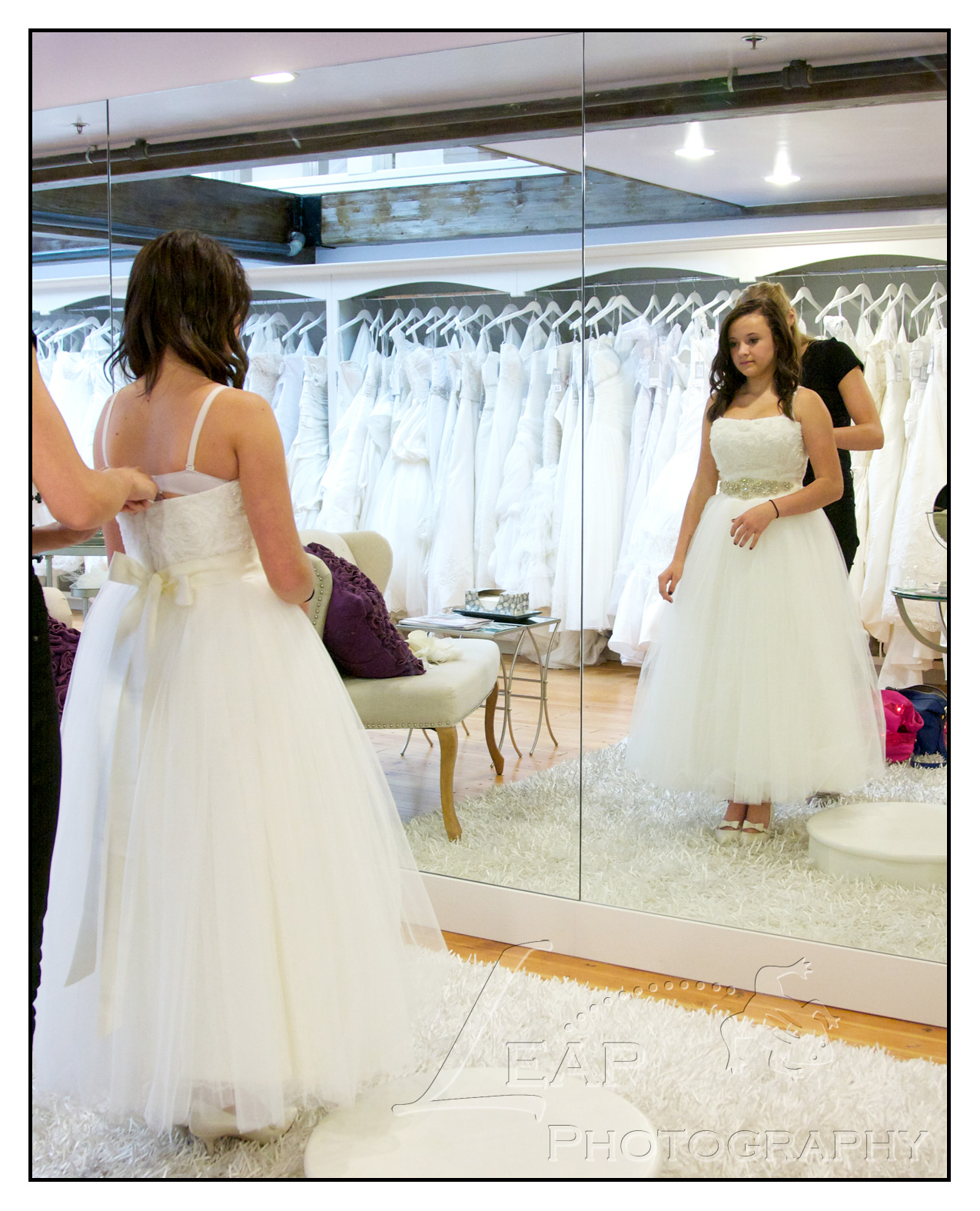 girl trying on bridal gown