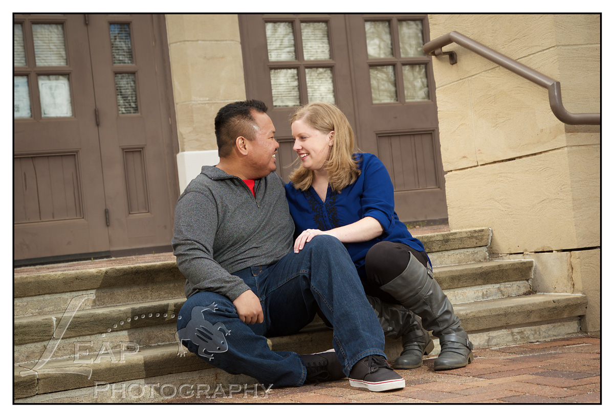 Engaged couple laughing on steps