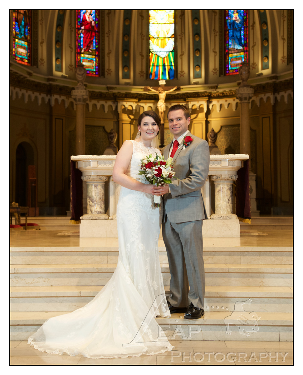 bride and groom on catholic church alter