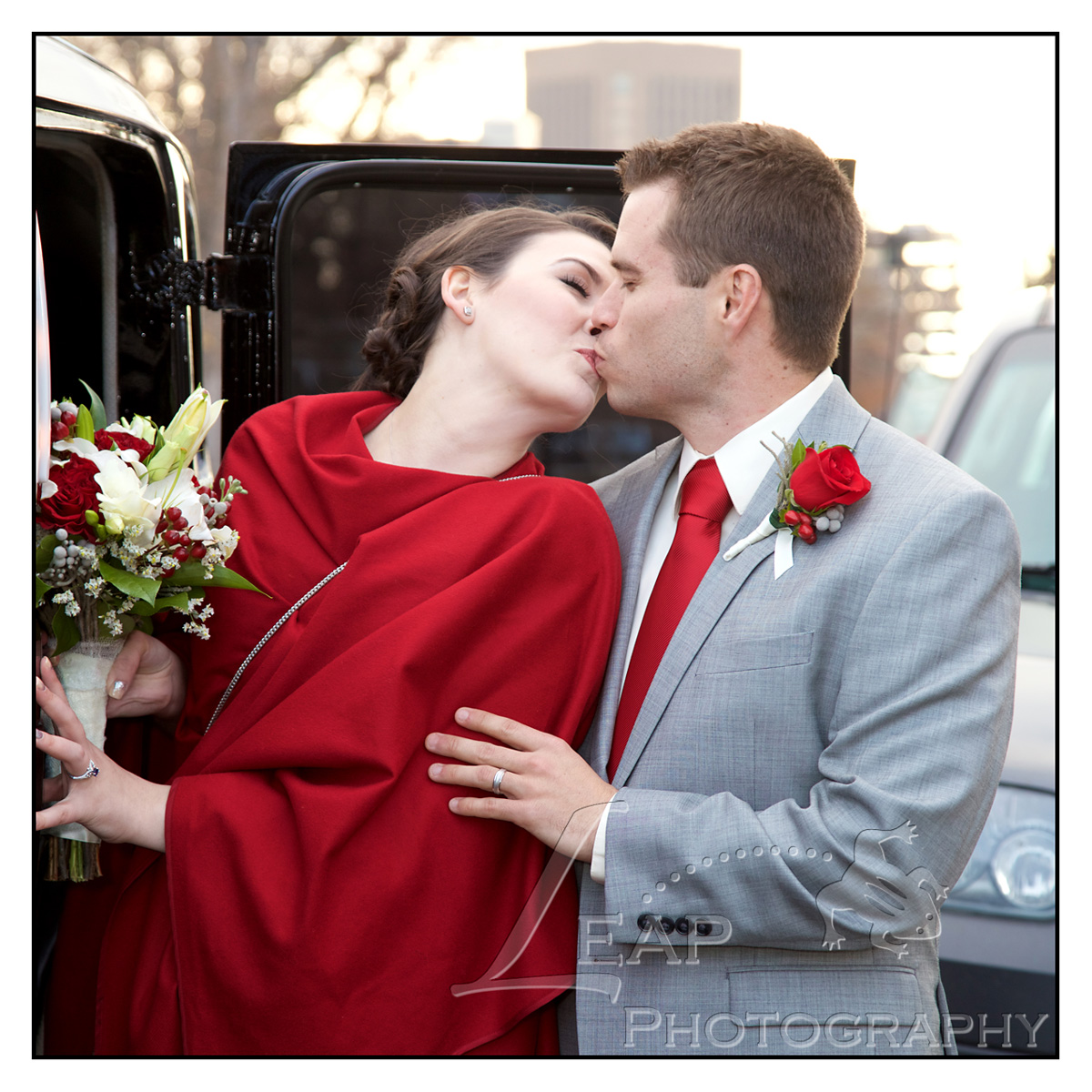 Newly wed couple kissing while getting in limo