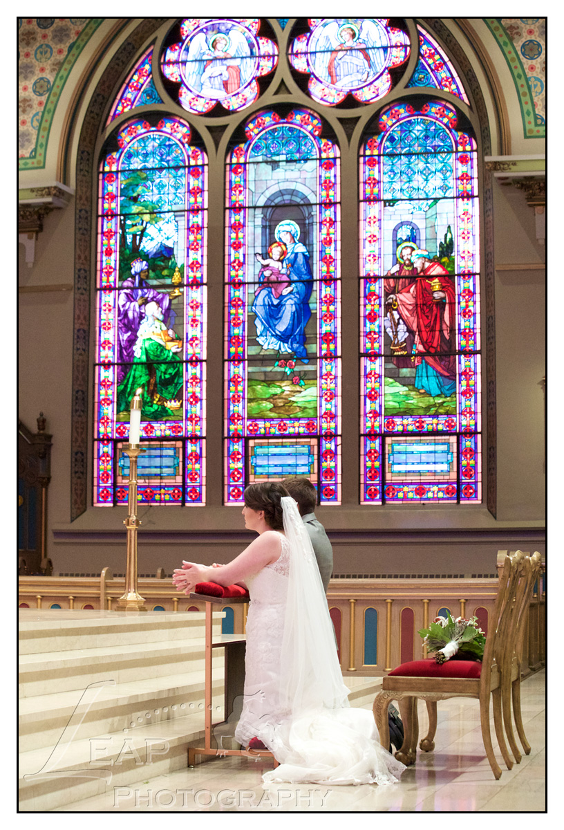 bride and groom kneeling in front of stained glass windows