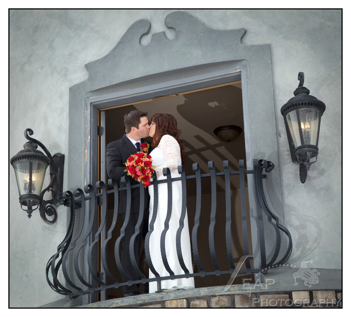 couple kissing in front of castle doors on their wedding day