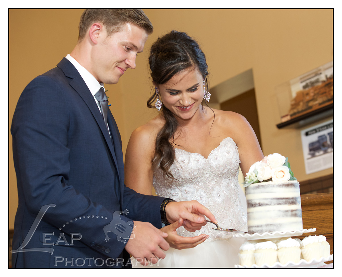 newly married couple cutting wedding cake