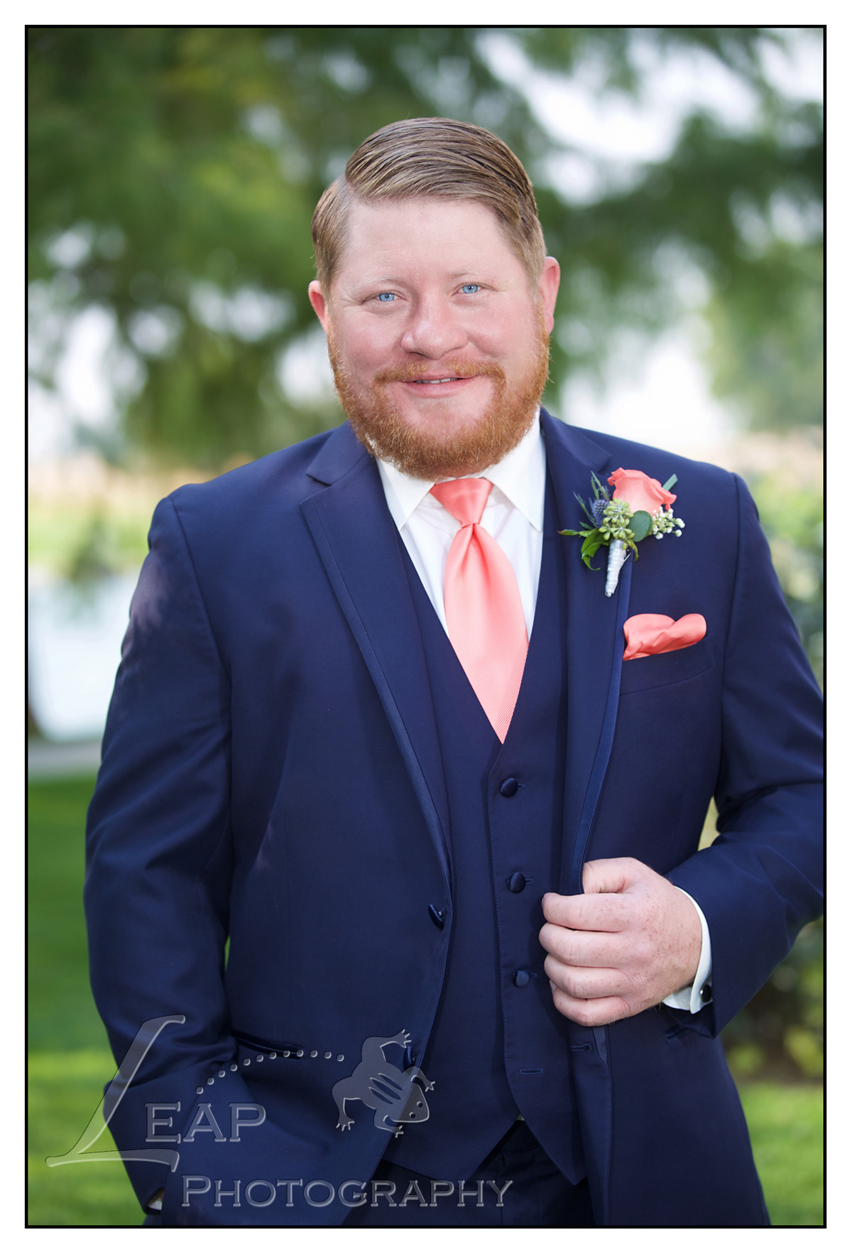 groom in navy suit with corral tie