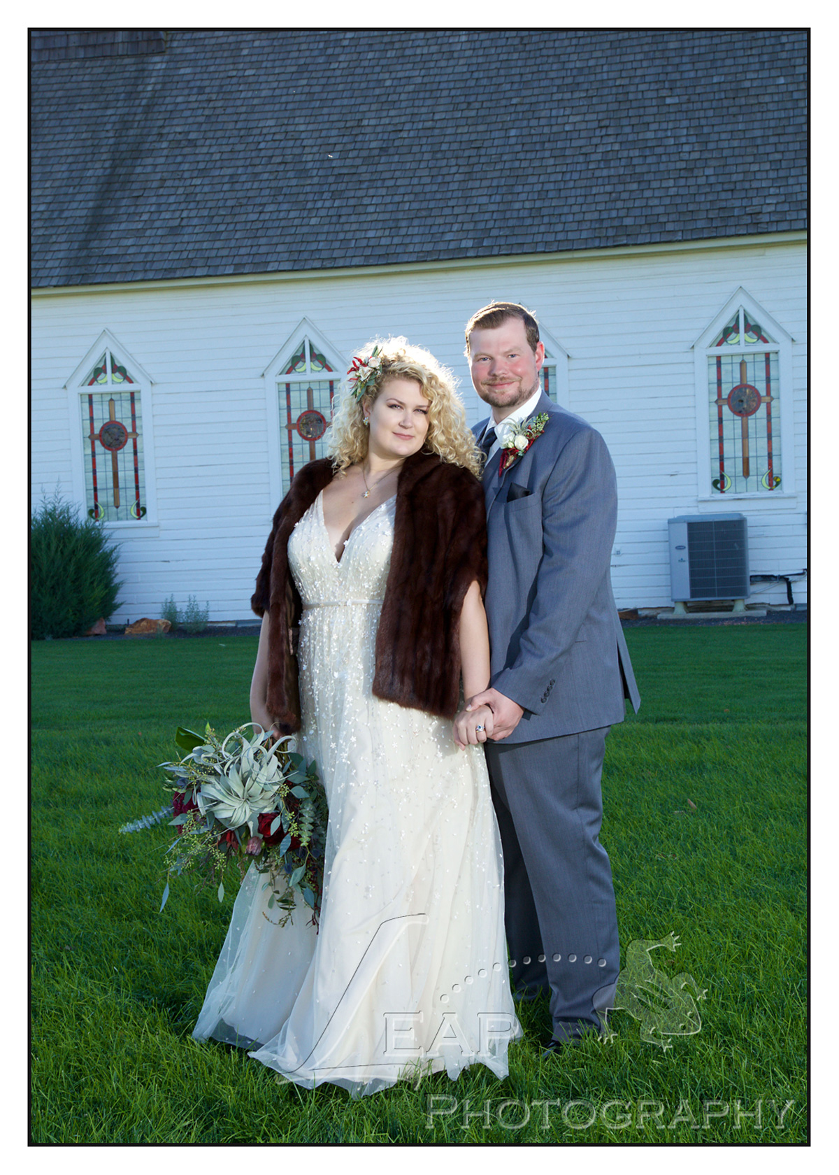wedding photo of couple beside old church