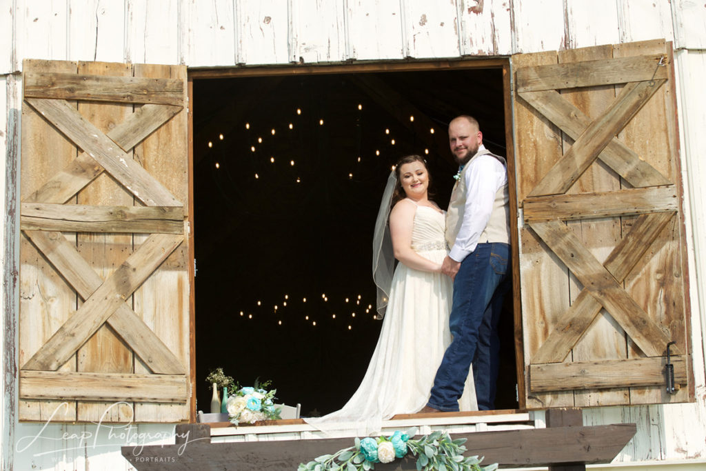 wedding picture of couple in hayloft doors