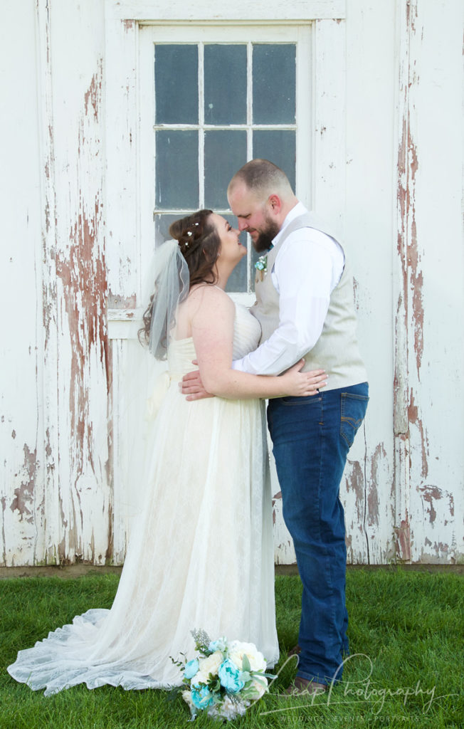 wedding portrait of couple in front of white barn