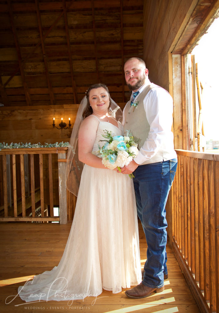 marriage photo of bride and groom inside barn