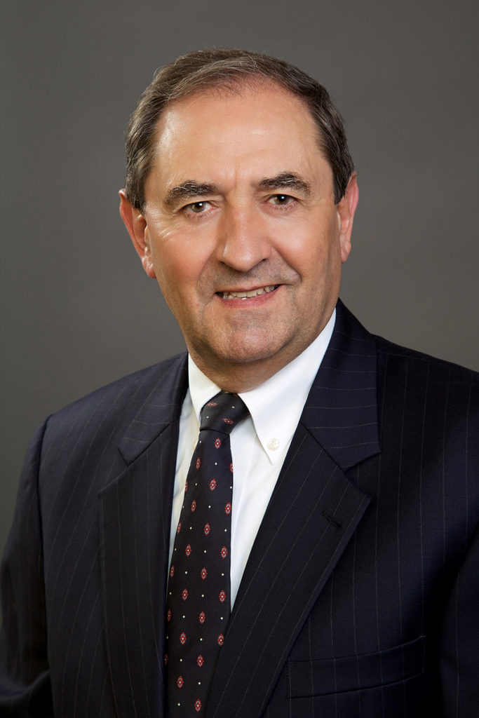 corporate headshot of a male wearing a suit and tie, photographed on a gray background