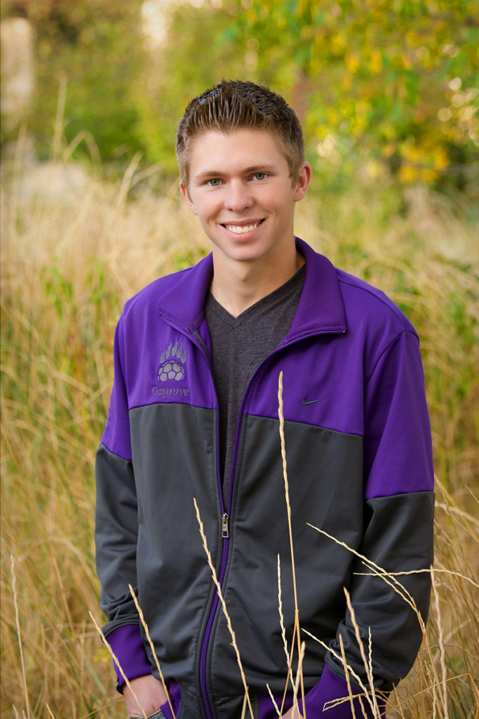 graduation photo shoot of male soccer player standing in tall grass