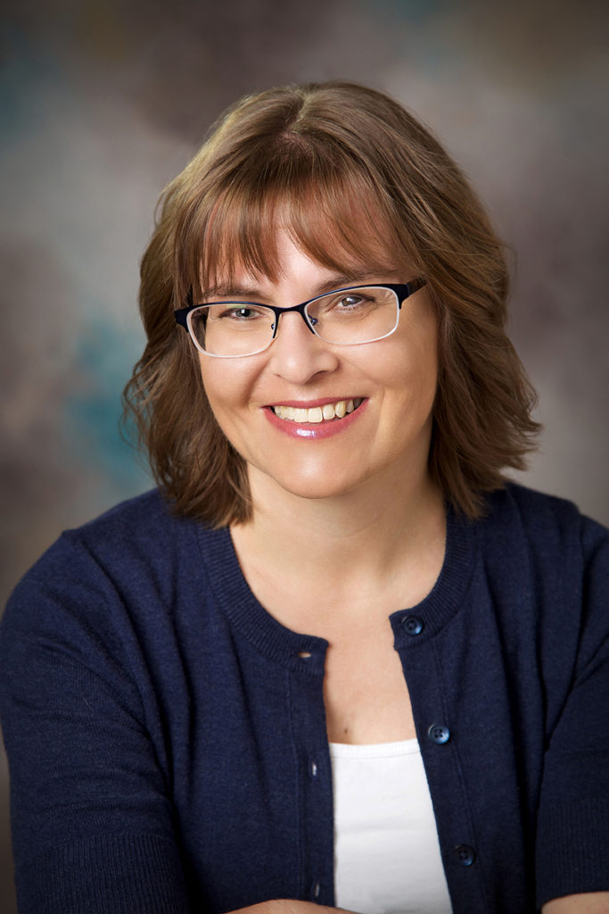 A professional studio headshot of a Boise female wearing casual attire