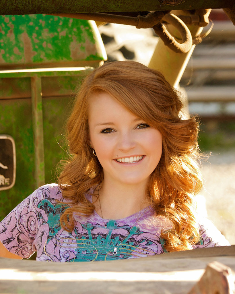 senior photos of boise female standing in front of John Deere Tractor