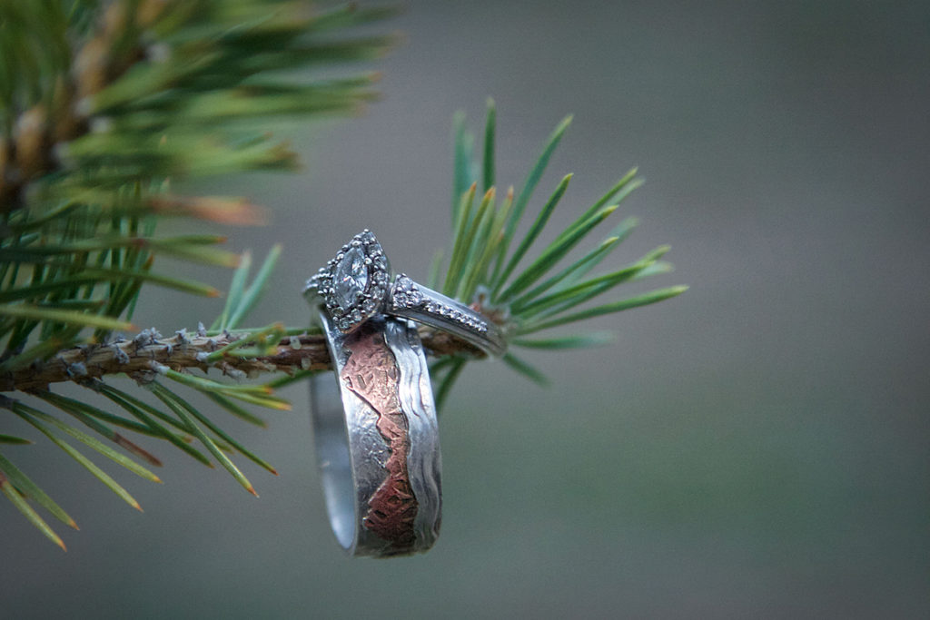 wedding rings hanging on a pine branch at an Idaho wedding