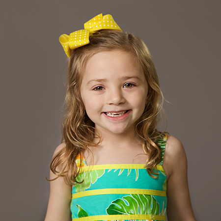 4 year old girl in sundress with bow in her hair